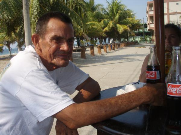 elderly man drinking soda palm trees
